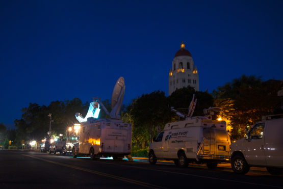 Media vans parked on street with Hoover Tower in background