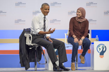 Barack Obama gesturing like he is holding a phone while talking with Mai Medhat