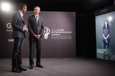 Sundar Pichai and Barack Obama speaking with a screen showing a young woman in the background.