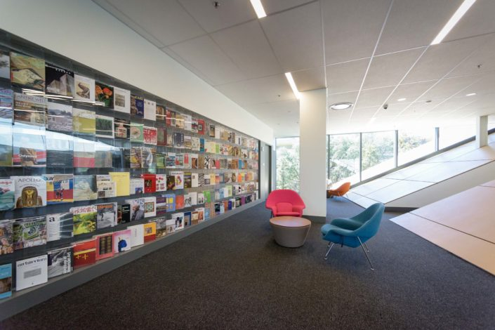 A colorful wall of periodicals on the left, with an entryway set in a steeply sloped wall on the right. In between are upholstered armchairs – one tangerine, another turquoise – with a small, low round table in between. (Image Credit: L.A. Cicero)