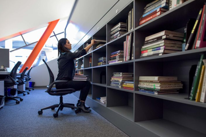 Alexandria Brown-Hedjazi, an art history graduate student, dressed in black, sits on an office chair in her carrel, a pile of books in her lap. She leans forward to lift a book from her bookcase. (Image Credit: L.A. Cicero)