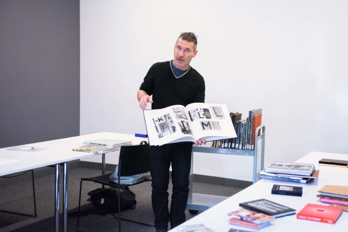 Professor Lukas Felzmann dressed in black, with eyeglasses on the top of his head, stands between two tables in a classroom filled with natural light, pausing in the middle of turning the pages of a large photographic book. One of the tables is strewn with a dozen books and a metal cart behind him holds a dozen more. (Image Credit: L.A. Cicero)