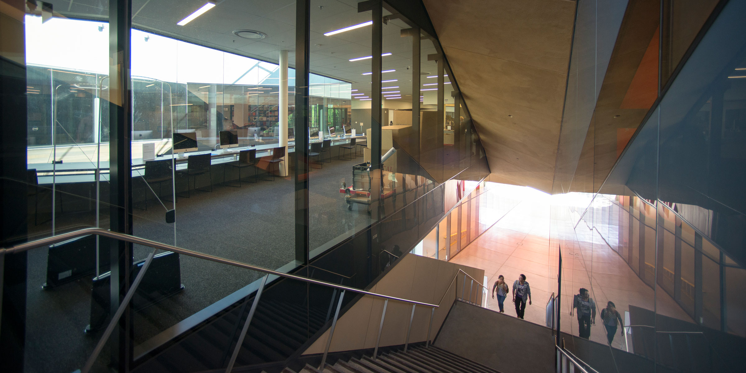 Two people ascending the covered staircase that leads to the library from the McMurtry Building's courtyard. The photo shows the floor-to-ceiling glass windows of the library, with a view of a long table that frames one side of the oculus. On the table are six desktop computers. (Image credit: L.A. Cicero)