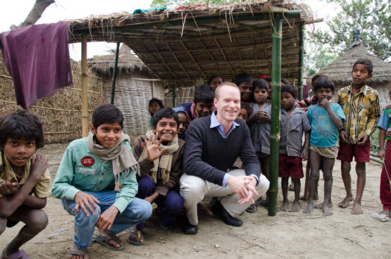 Grant Miller surrounded by children in India.