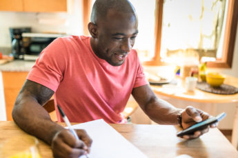 man doing paperwork at the kitchen table