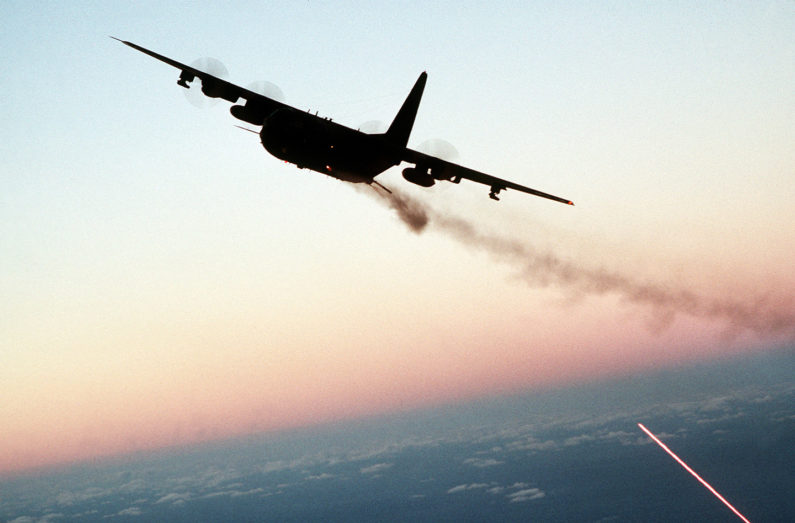 An AC-130 Hercules aircraft banks to the left