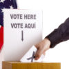 Hand inserting a ballot to voting box. The sign above the slot in two languages, English and Spanish. USA flag and white background.