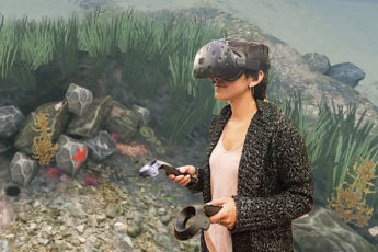 Researcher trying the Stanford Ocean Acidification Experience, a new virtual reality science education tool, with coral animation still in background.  Credit info:    Stanford Virtual Human Interaction Lab