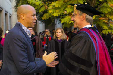 Corey Booker speaking as Marc Tessier-Lavigne listens.