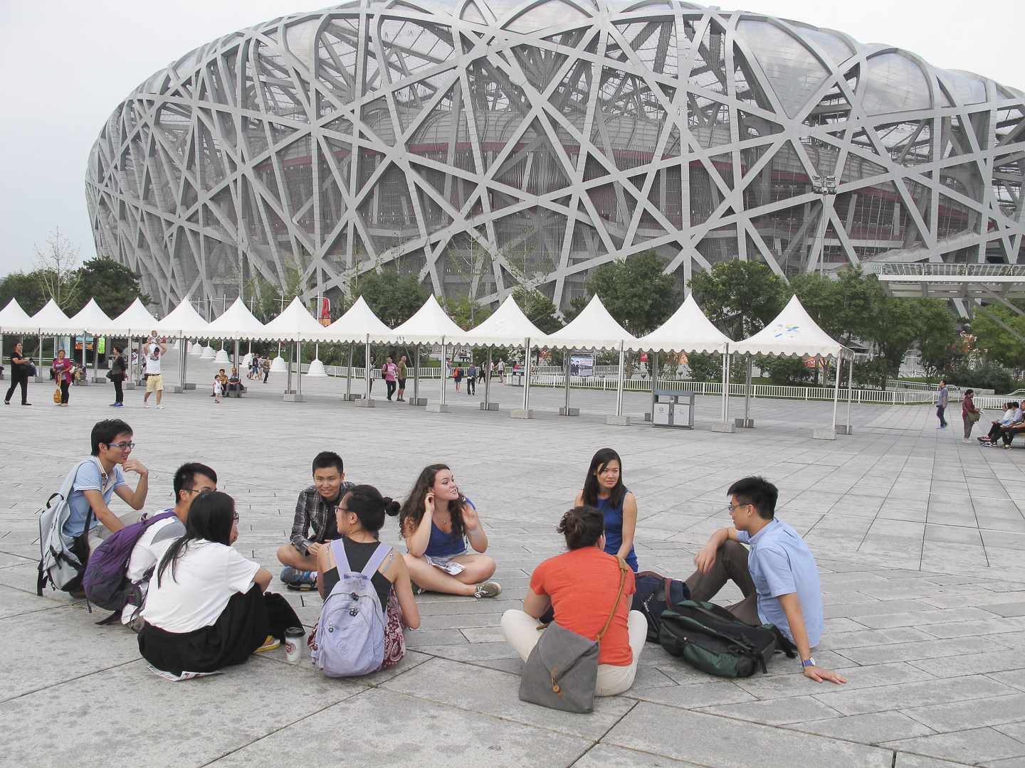 class sitting in discussion outside the Bird's Nest stadium at Olympic Village in Beijing