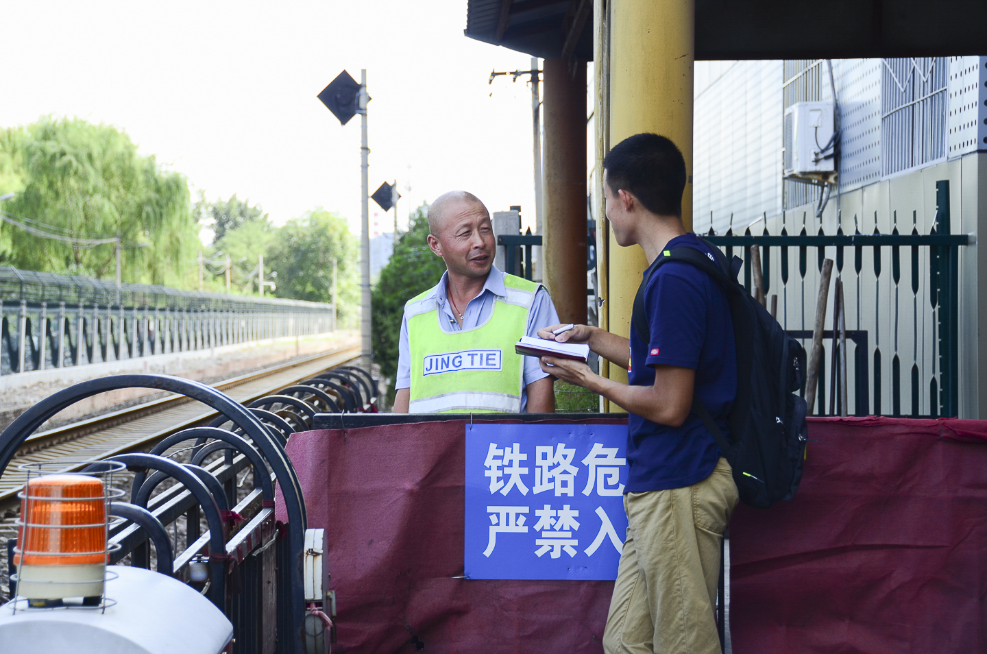 Student conducts fieldwork in Beijing by interviewing train station guard.