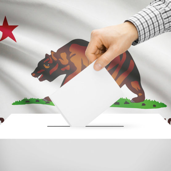 Ballot box with California state flag in the background.