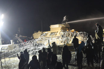 Law enforcement personnel fire a water canon at Standing Rock protesters in sub-zero temperature.