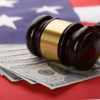 Close-up Of Wooden Brown Gavel On Usa Dollar Banknotes And American Flag