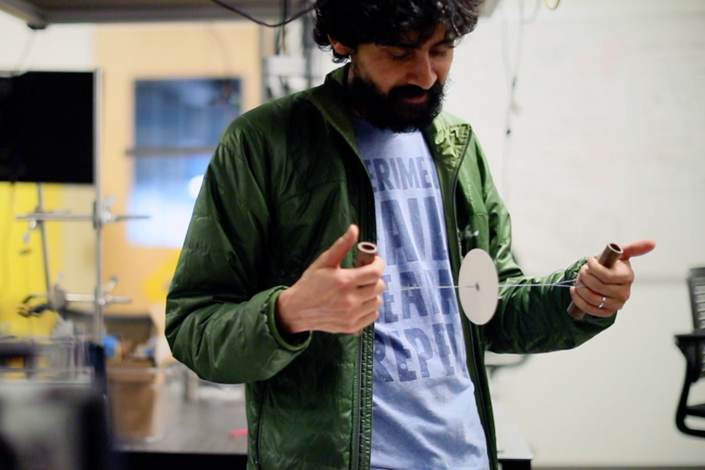 Manu Prakash with a spinning disc whirligig that can be used as a low-cost centrifuge