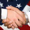 handshake with American flag in background