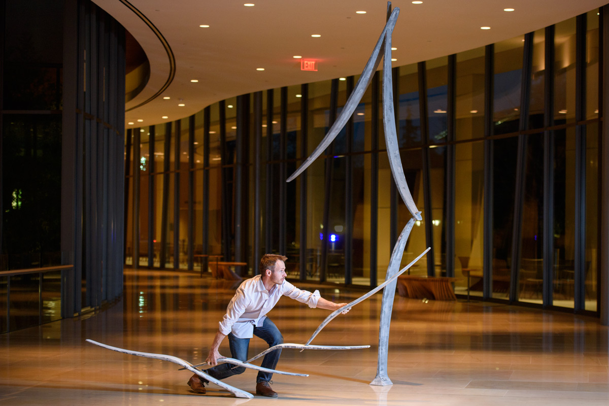 Sculptor Will Clift adjusts the placement of his sculpture before a rehearsal at the Bing Concert Hall.