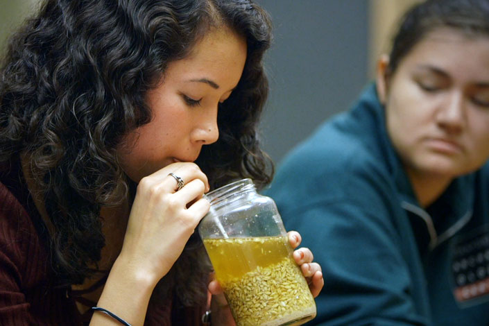 Student sipping through a straw a self-brewed beer from an ancient recipe