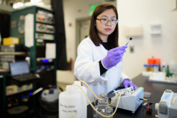 Chong Liu examines a carbon-amidoxime electrode before assembling it into the flow device.