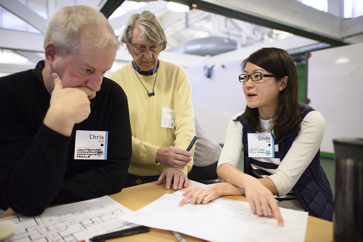 Chris Ford, Larry Leifer and Sindy Tang around a desk working on an exercises in the Catalyst workshop.