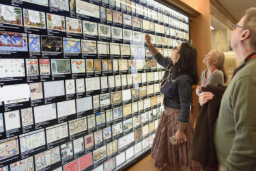 family members looking at a wall of maps