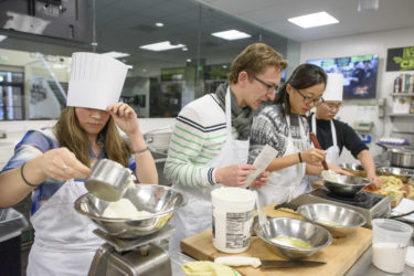 members of class in kitchen measuring ingredients