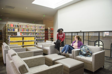 students chatting in a study area near the skylight in Li & Ma Science Library