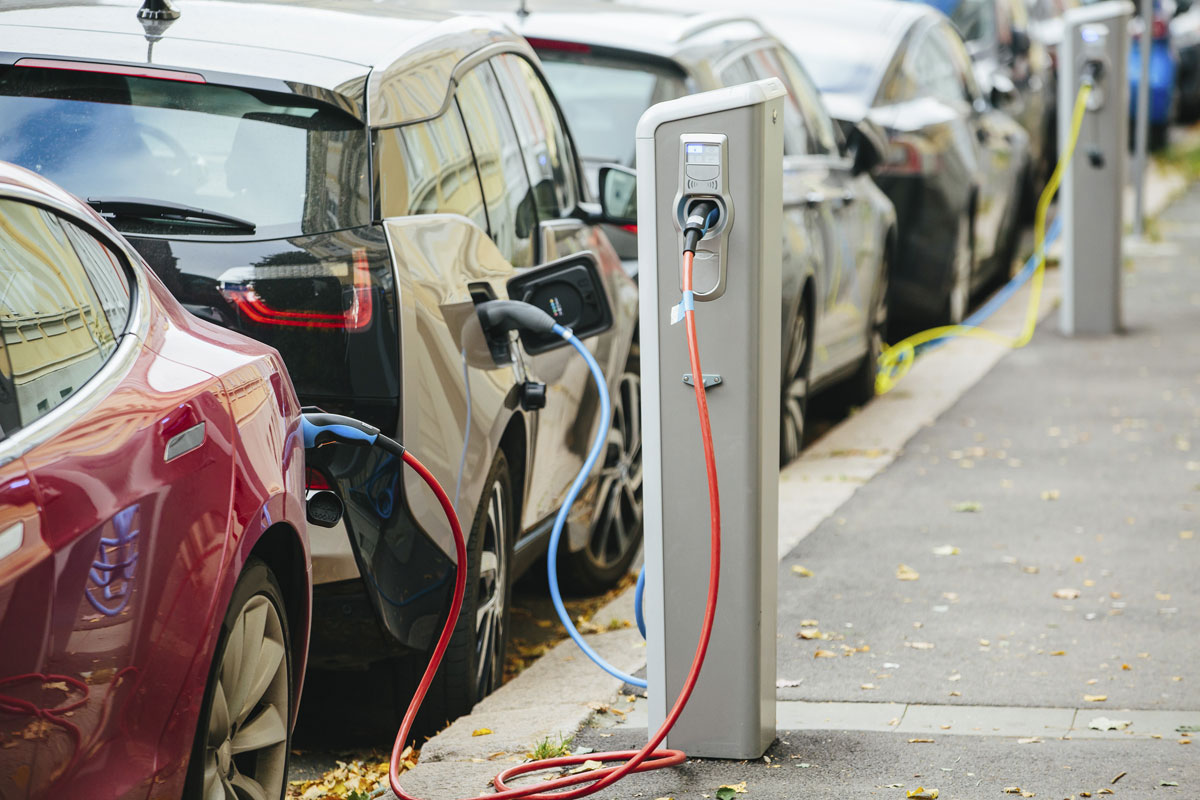 Electric vehicles plug in to charging stations. New research may accelerate discovery of materials used in electrical storage devices, such as car batteries.
