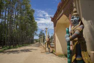 A view down a dirt road, with trees on the left, and the entrance to a temple on the right. Two ornate statues flank the temple entrance.