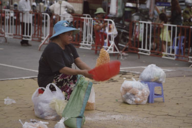a woman seated on the ground, tossing corn in large plastic bowl