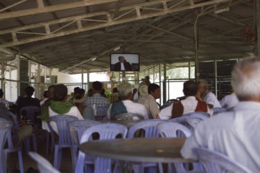 a room full of people watching a televised trial