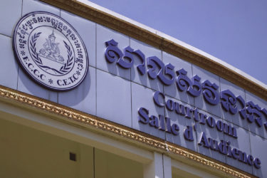 "sign above the entrance to the courthouse, with ""Courtroom"" written in Khmer (Cambodian), English and French"