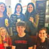 Six students posing with reusable coffee cups