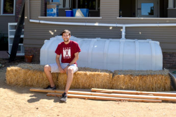 Student Andrew Jacobs sits on a water catchment system behind a house