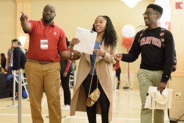 Assistant Dean of Diversity Femi Ogundele assists N'Naserri Carew-Johnson and Jonathan Johnson, admits who both graduated from the same high school in Atlanta.