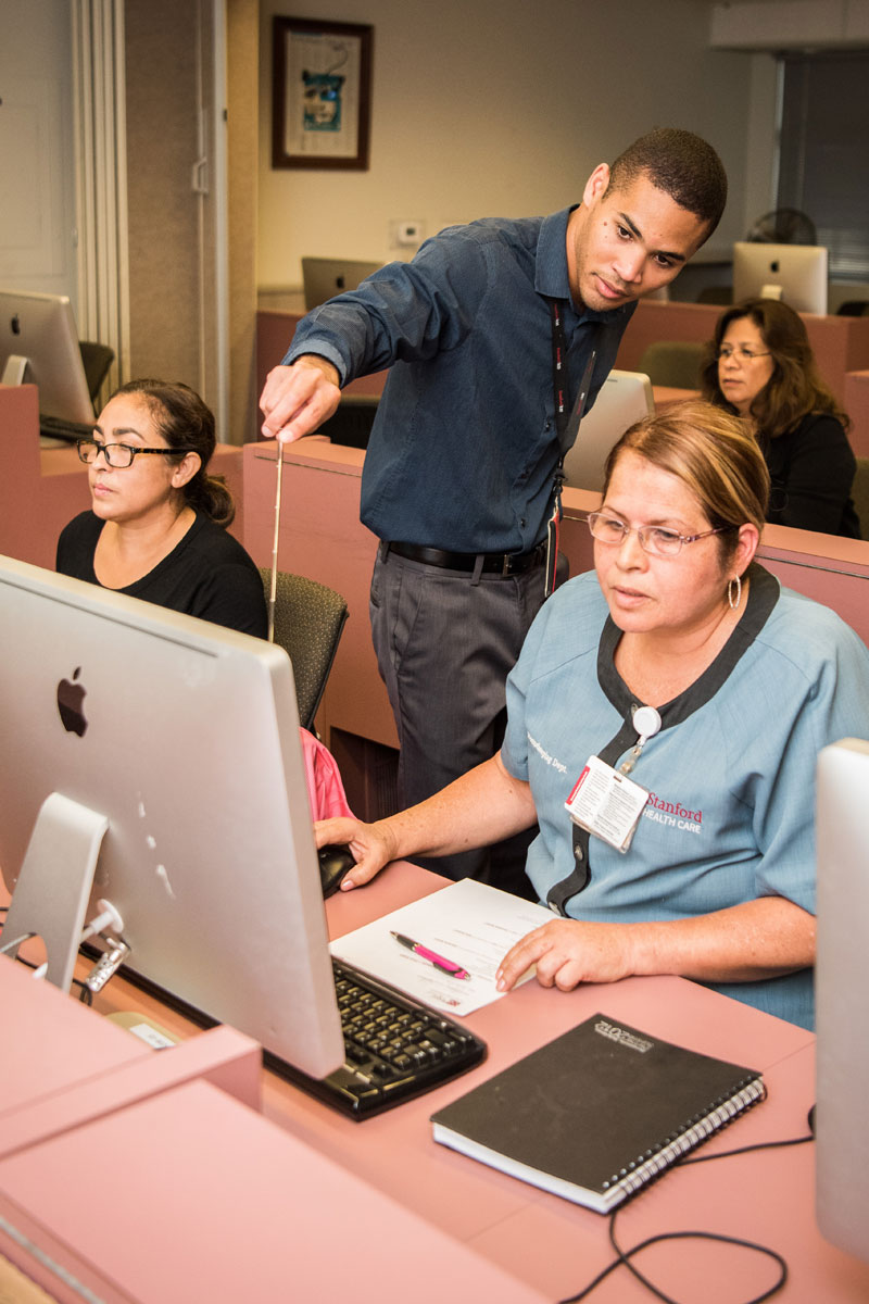 Stepping Stones to Success teacher Frank Larteri assists Stanford Health Care employees in a computer class.