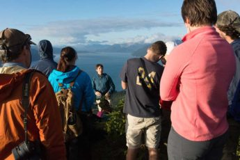 Instructor Zach Brown talking to students at the water's edge in rural Alaska