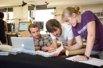 Graduate students Joseph Greer, left, and Laura Blumenschein, right, work with Elliot Hawkes, a visiting assistant professor