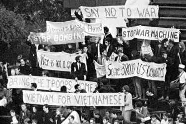 Students holding protest signs at a football game