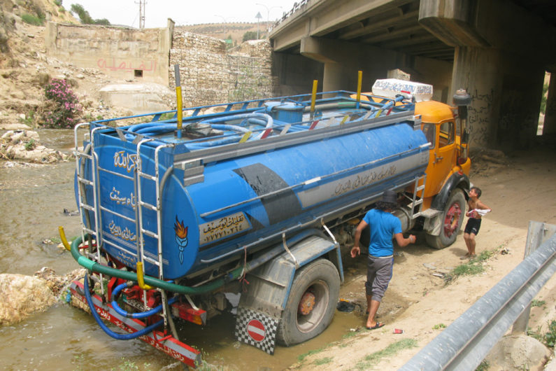 A tanker truck illegally takes water from a river in Jordan.