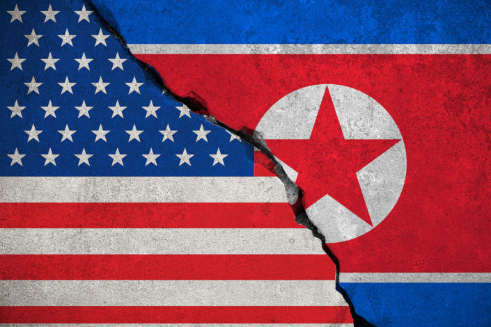 illustration of a cracked concrete wall with images of U.S. and North Korean flags