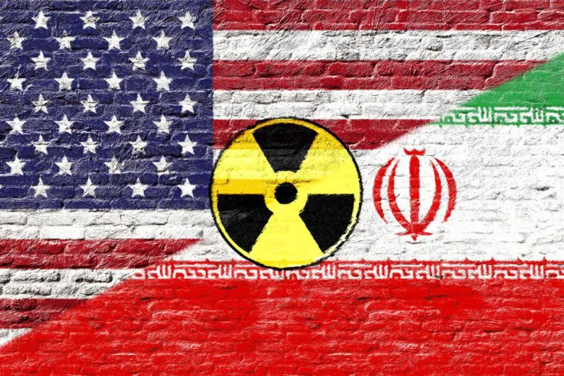Iranian and U.S. flags with nuclear logo
