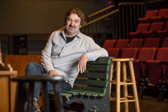 Branislav Jakovljevic sitting on a bench in a theater