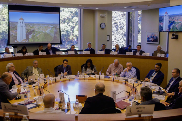 scholars at a Hoover Institution conference seated in a circular meeting room