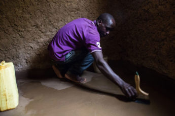 One of EarthEnable's most experienced masons, Theophile Ngirukwayo, applies the company's proprietary waterproof varnish to a home in Rwanda's Bugesera District.