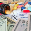 prescription bottle with pills spilling out over scrip and money