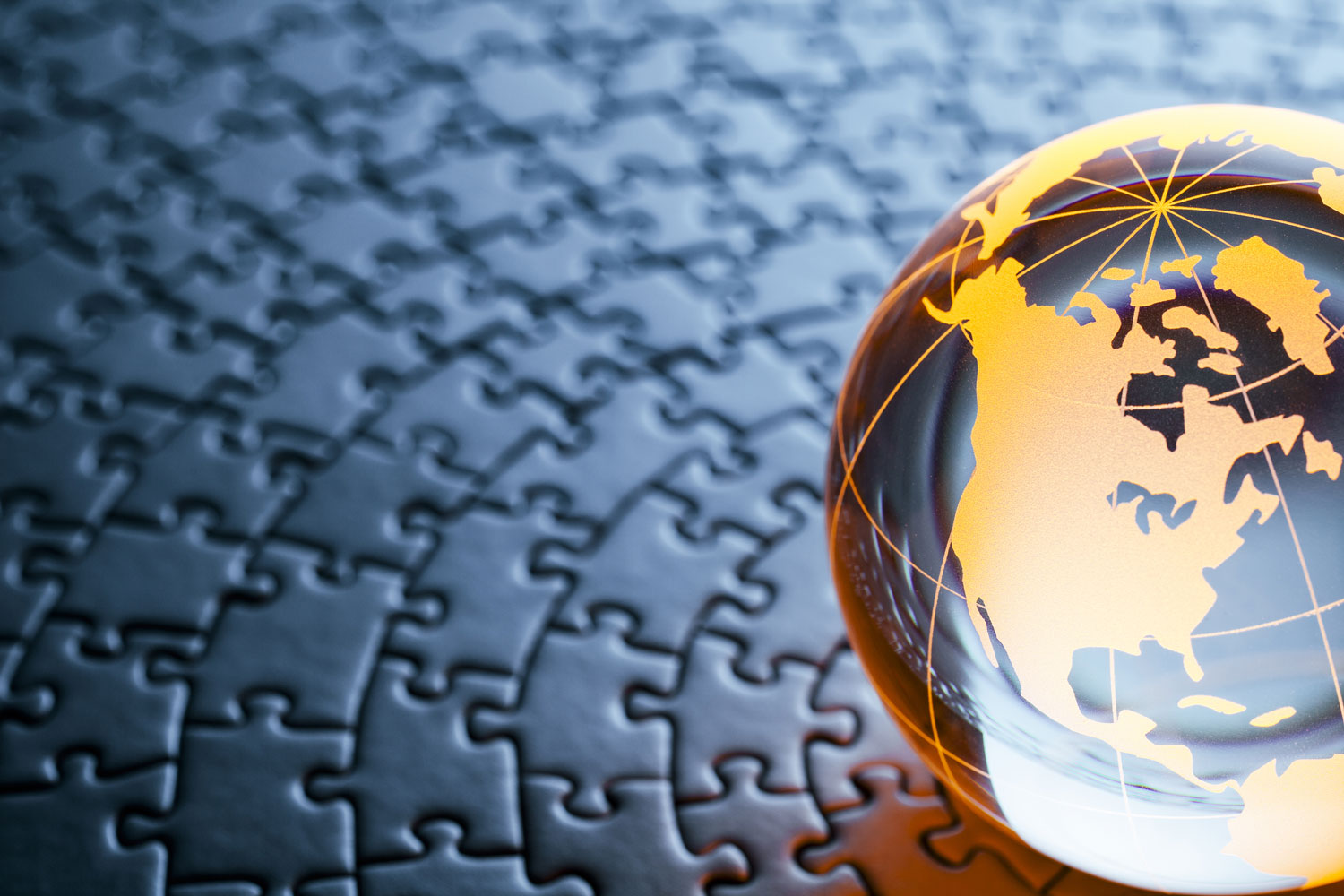 a crystal globe featuring North America sitting on a jigsaw puzzle background
