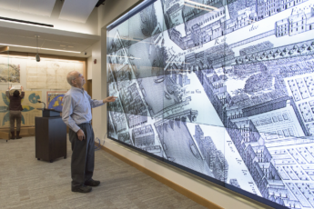 David Rumsey examines a historical map of Paris in the David Rumsey Map Center in Green Library.