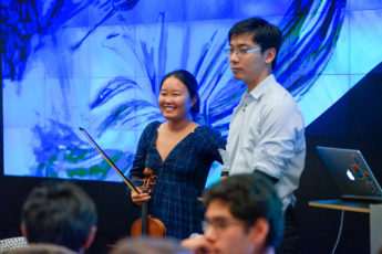 """Classical improvisational violinist and scientist Lucy Liuxuan Zhang and creative coder Xiaohan Zhang participate in the interdisciplinary performance """"Drawing with Gravitational Waves,"""" created by artist and Stanford design lecturer Pamela Davis Kivelson."""