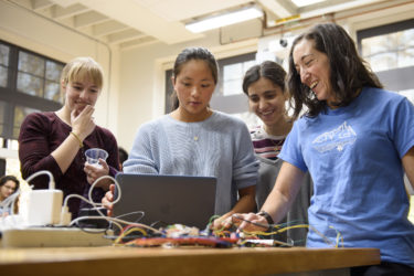 Grad student Laura Blumenschein, left, observes Grace Zhao and Goli Emami's project which gives haptic feedback while navigating a maze. Cara Welker, right, a grad student in bioengineering tests the device.